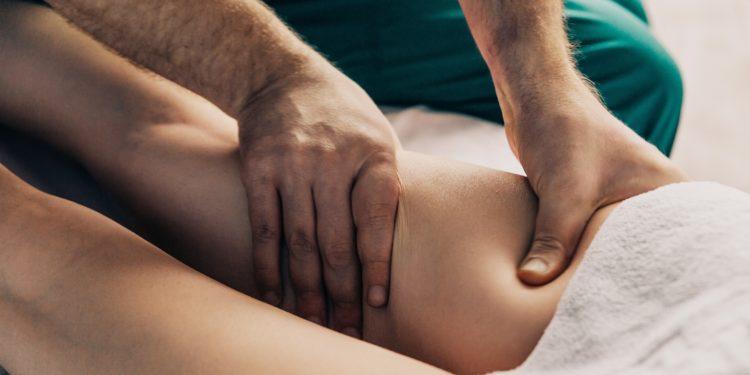 Ein Therapeut führt eine Lymphdrainage am hinteren Oberschenkel einer Frau durch.