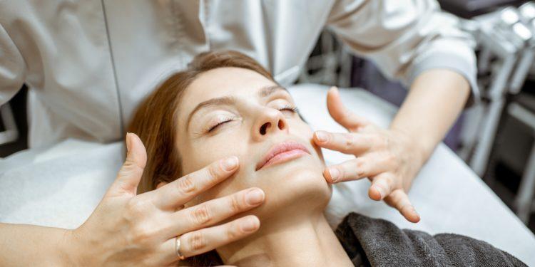 Therapeutin führt eine Lymphdrainage im Gesicht einer Frau durch.