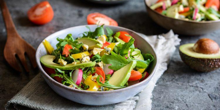 Drei Teller mit gemischtem Salat und eine aufgeschnittene Avocado und Tomate daneben