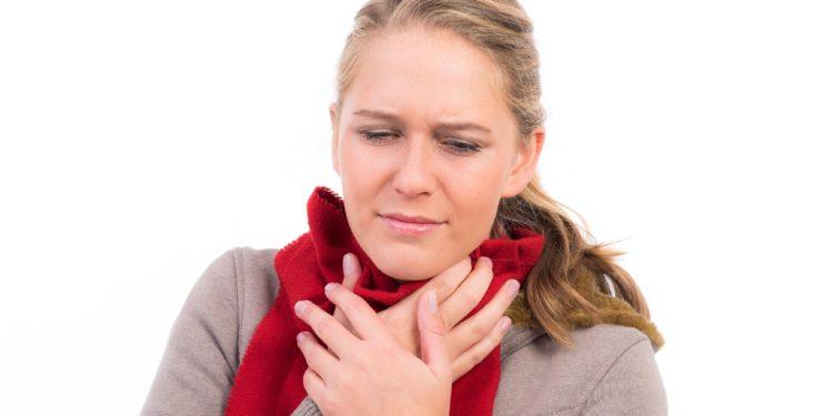 Eine Frau mit umgebundenem Schal hält sich die Hände an den schmerzenden Hals.