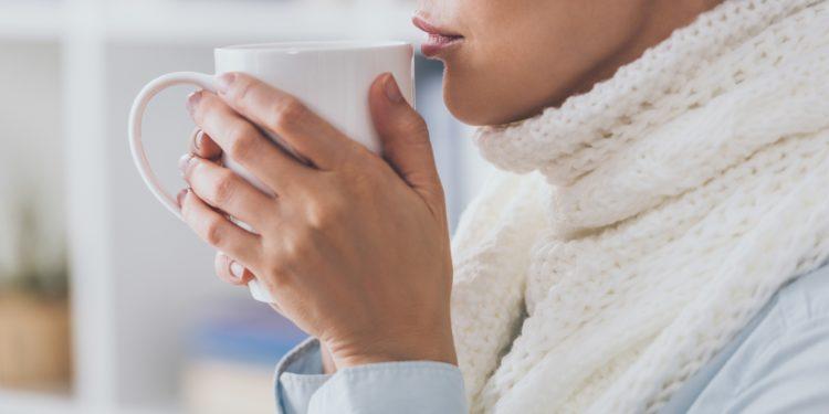 Eine Frau mit dickem Schal um den Hals hält einen Becher mit warmem Tee in den Händen.