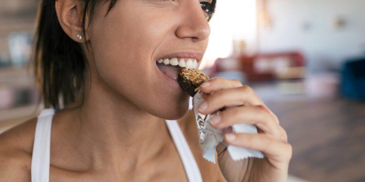 Sportliche junge Frau isst einen Müsliriegel