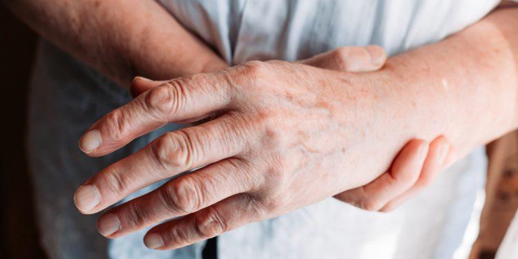 Ältere Frau hält ihr von Rheuma-Schmerzen geplagtes Handgelenk