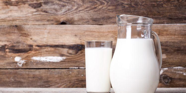 Milch in einem Krug und in einem Glas auf einem alten Tisch