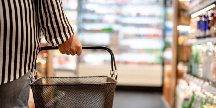 Frau mit Einkaufskorb in einem Supermarkt