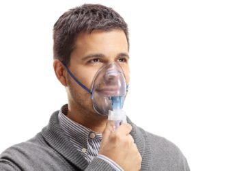 Ein Mann mit einer Sauerstoffmaske über Nase und Mund.