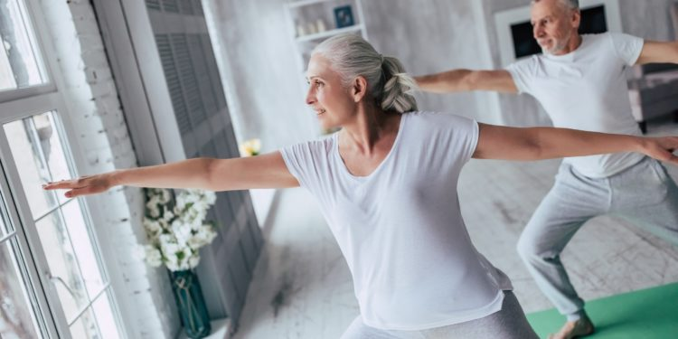 Ein älteres Paar führt zu Hause Gymnastikübungen durch.