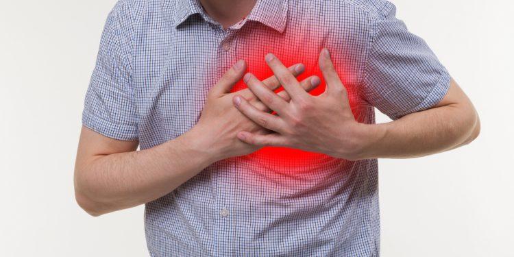 Ein Mann fasst sich mit beiden Händen an die linke Brust.