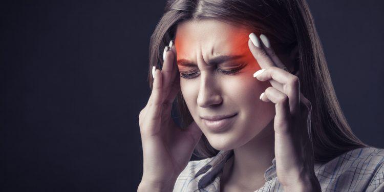 Eine Frau mit schmerzverrtem Gesicht hält sich die Hände an die Schläfen.