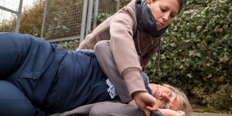 Eine junge Frau prüft den Puls bei einer bewusstlosen Frau.