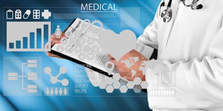 Im Vordergrund sind verschiedene medizinische Begriffe und Symbole abgebildet, im Hintergrund füllt ein Mediziner in weißem Kittel ein Formular auf einem Klemmbrett aus.
