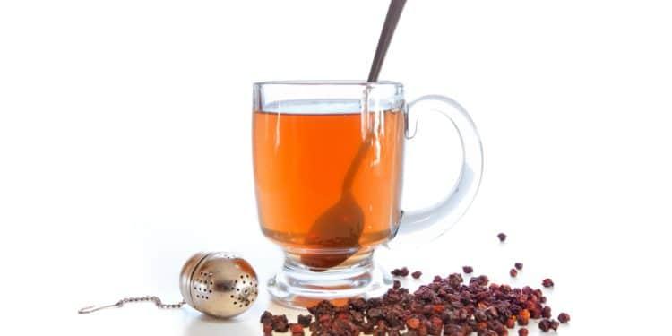 Ein Glas mit Schisandra-Tee, daneben ein Tee-Ei und einige Schisandra-Beeren.