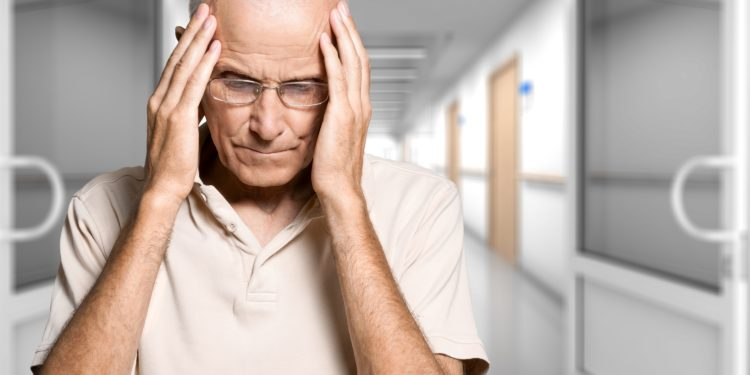 Älterer Mann hält sich seine Hände an den Kopf