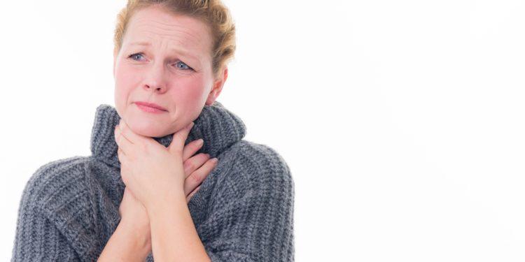 Eine Frau hält sich beide Hände an den schmerzenden Hals.