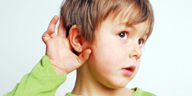 Ein kleiner Junge klapptmit der Hand sein Ohr etwas nach vorne, um besser hören zu können.