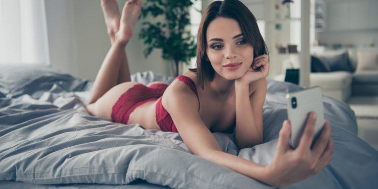 Eine Frau in Unterwäsche liegt auf dem Bett und macht ein Selfie.