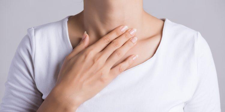 Eine Frau fasst sich mit einer Hand an den Hals