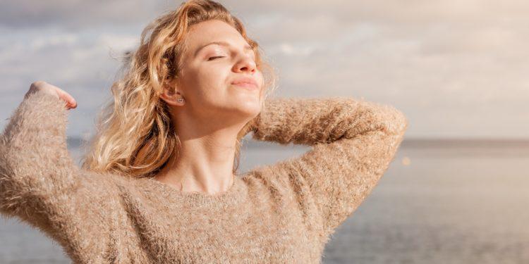 Eine Frau steht am Strand und genießt die Sonne.