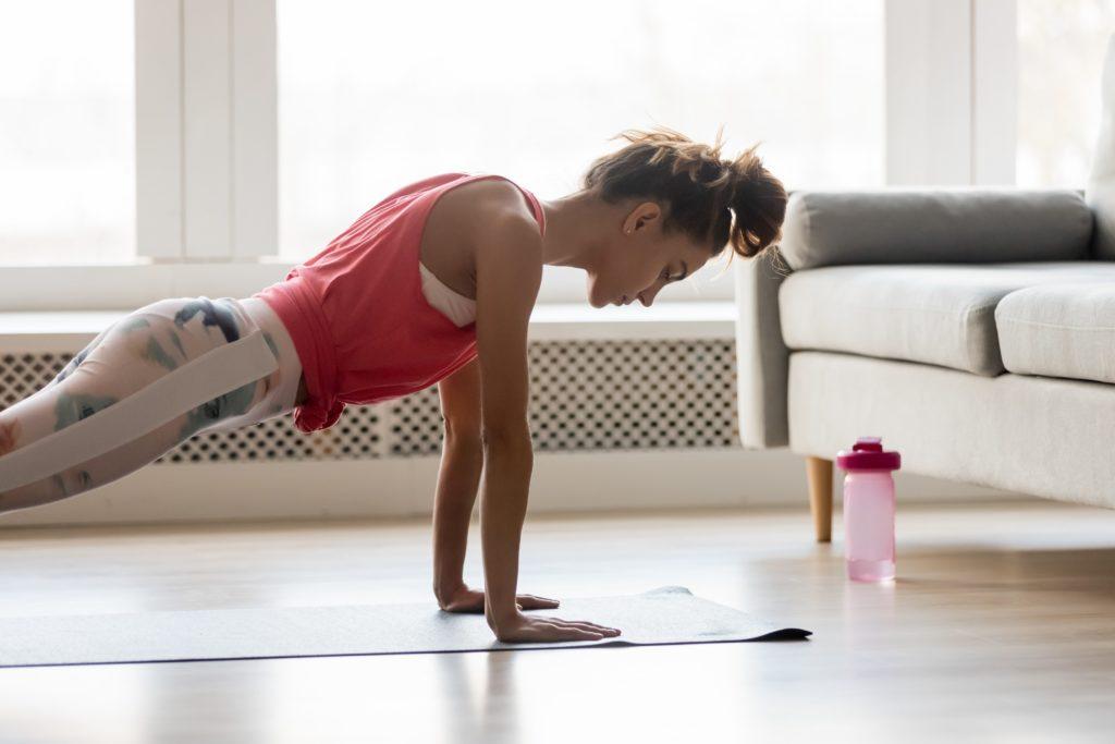 Eine Frau in Sportkleidung macht zu Hause Liegestütze auf einer Matte.
