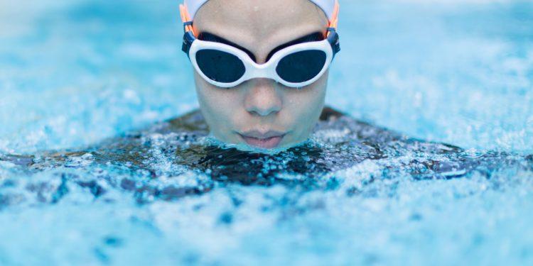 Eine Frau mit Schwimmbrille und Schwimmkappe beim Brustschwimmen.