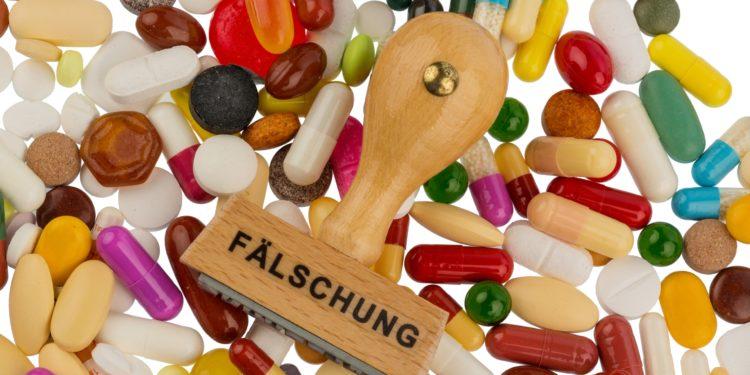 Stempel mit dem Aufdruck Fälschung auf bunten Tabletten