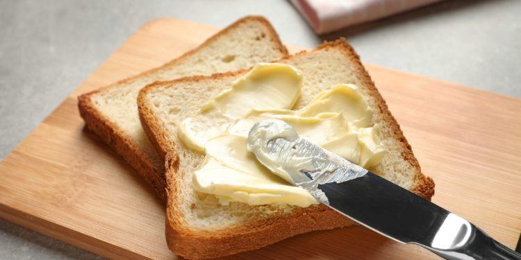 Toast liegt auf einem Brettchen und wird mit Margarine bestrichen.