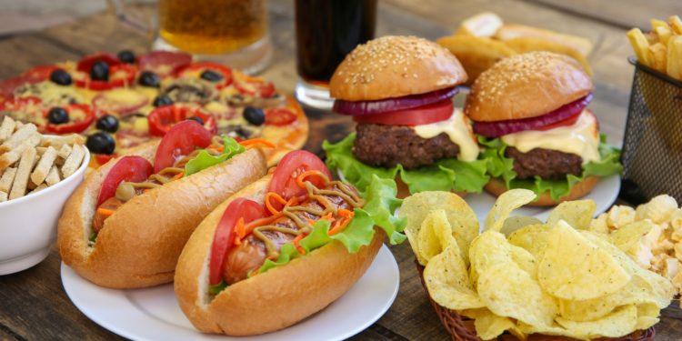 Burger, PIzza, Chips, Pommes, Hot Dogs, Cola und Bier auf einem Holztisch.