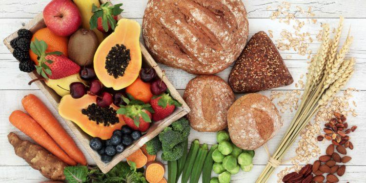 Auf einem Holztisch steht eine Kiste mit verschiedenen Obstsorten, daneben liegen verschiedene Gemüse, Vollkornbackwaren und Nüsse.
