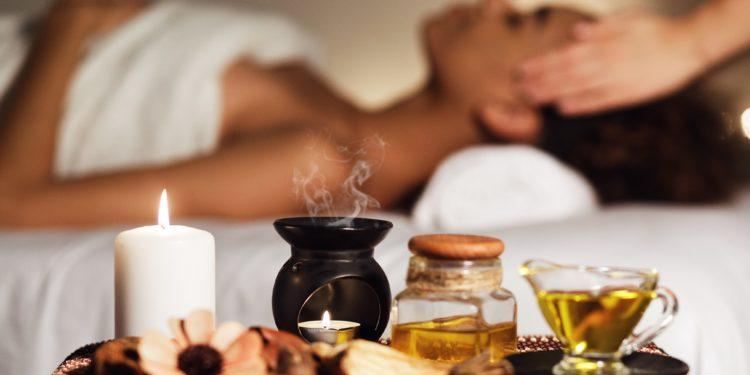 Eine Frau erhält eine Massage, die mit ätherischen Ölen unterstützt wird.