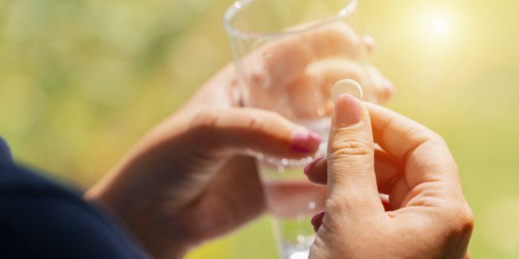 Eine Frau hält in einer Hand eine Tablette und in der anderen ein Glas Wasser