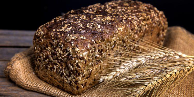 Ein Laib Vollkornbrot mit einer Getreideähre daneben