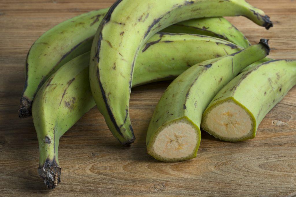 Ganze und halbe grüne unreife Bananen auf einem Tisch