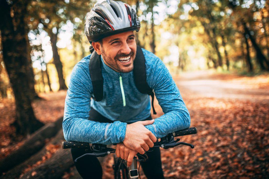 Junger Mann mit Helm auf seinem Fahrrad