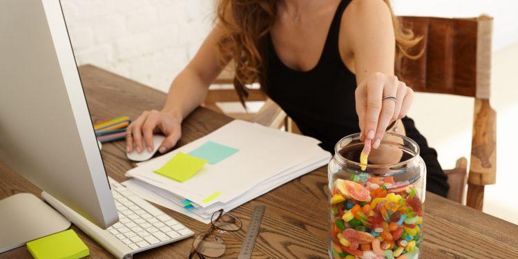 Frau mit Süßigkeitenglas neben ihrem Arbeitsplatz.
