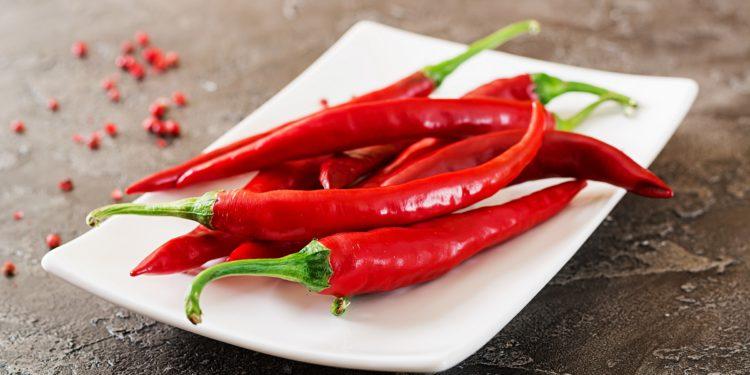 Einige rote Chilis liegen auf einem weißen Teller.