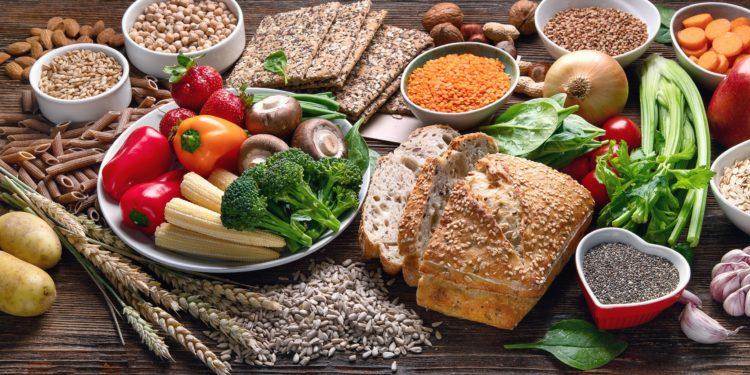 Verschiedene Lebensmittel wie Obst, Gemüse, Knäckebrot und Vollkornnudeln auf einem Tisch