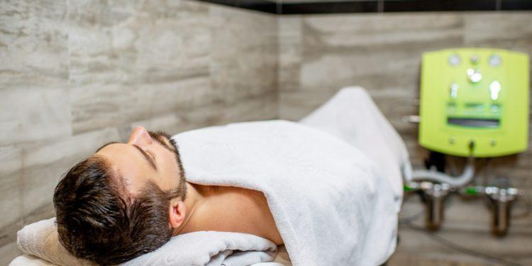 Ein Mann liegt zugedeckt auf einer Liege und ist über Schläuche mit einem Colon-Hydro-Therapie-Gerät verbunden.
