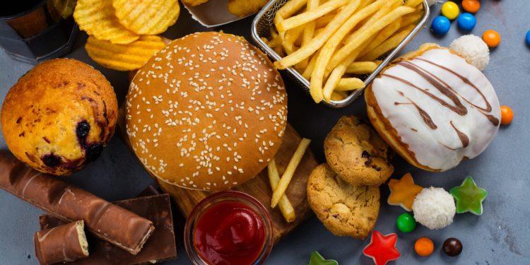 Eine Mischung verschiedener ungesunder Nahrungsmittel wie Pommes, Chips, Kuchen und Süßigkeiten.
