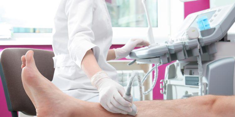 Ärztin führt bei einem Patienten eine Ultraschalluntersuchung des Beins durch