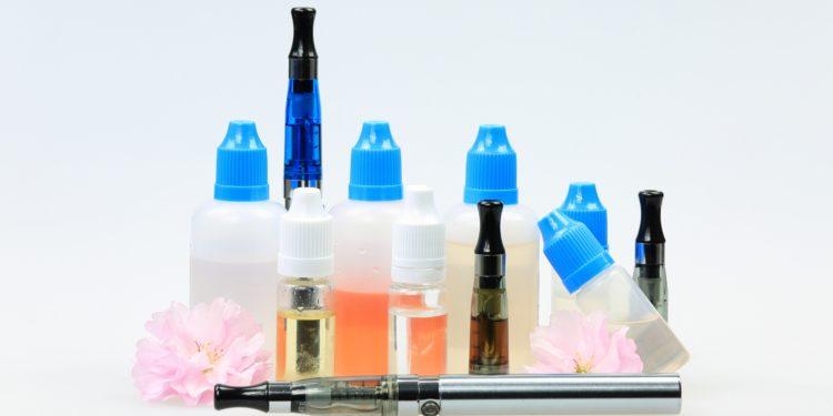 Eine E-Zigarette vor verschiedenen Liquids