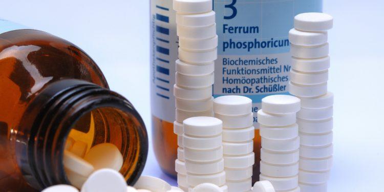 Gestapelte Schüßler-Salz-Tabletten mit Schüßler-Salz-Flasche Ferrum Phosphoricum