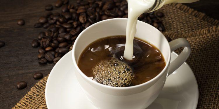 Milch aus einer Glasflasche wird in eine Tasse Kaffee gegossen