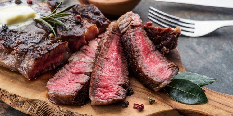 Medium rare Steak aufgenschitten auf einem Holzbrett mit Pfefferkörnern, Messer und Gabel daneben