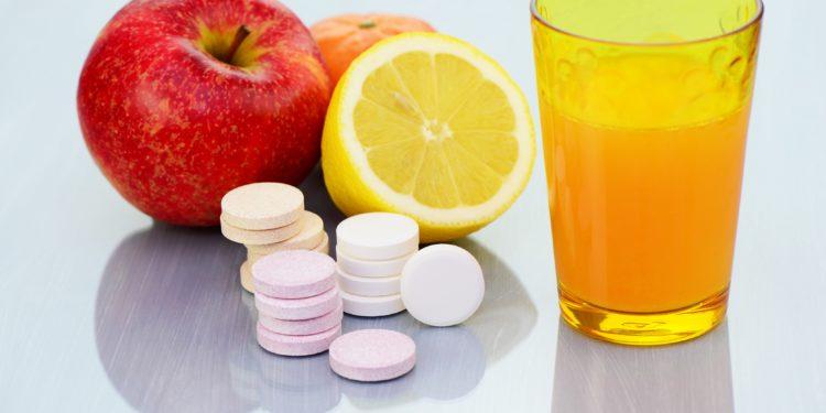 Zwei Äpfel, eine halbe Zitrone, einige Vitamintabletten und ein Glas Orangensaft
