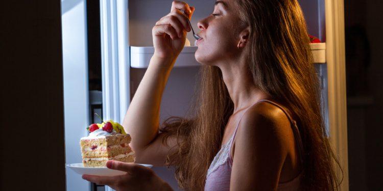 Eine Frau steht am Kühlschrank und isst ein Stück Kuchen.