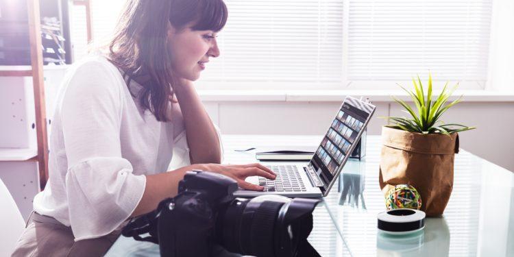 Junge Frau bearbeitet Fotos auf dem Laptop