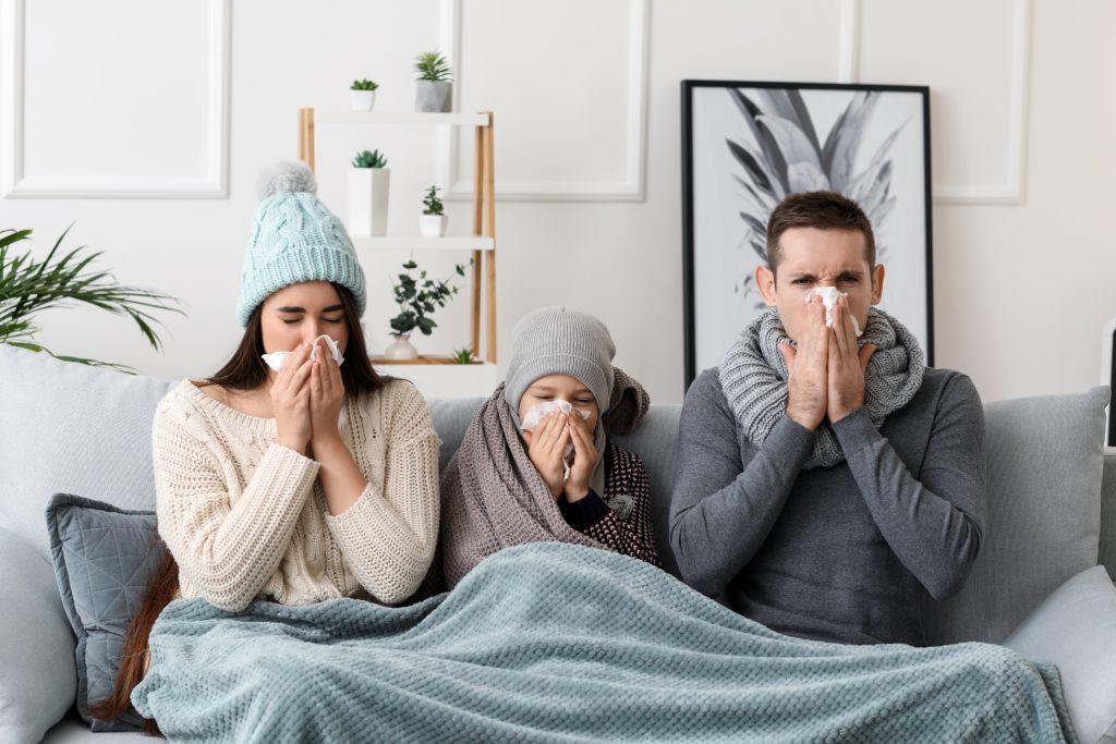 Eltern sitzen mit ihrem Kind auf dem Sofa - alle drei erkältet.