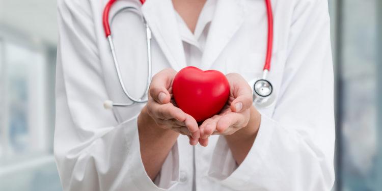 Arzt hält ein rotes Herz in seinen Händen