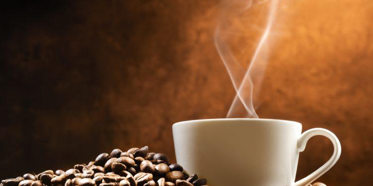 Kaffeetasse auf einem Haufen Kaffeebohnen.