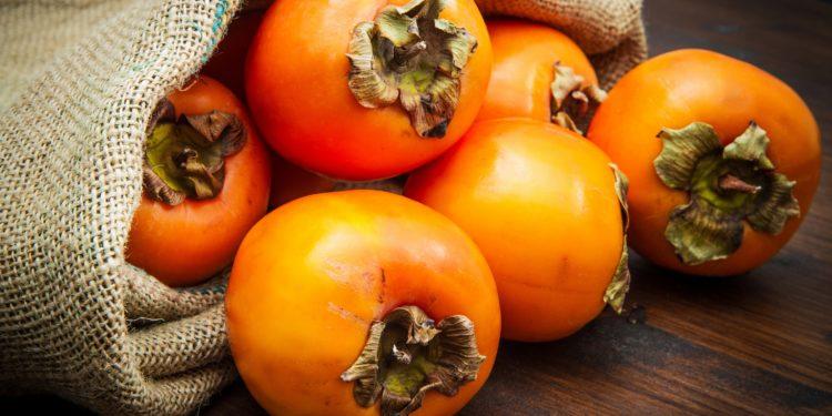 Frische Kaki-Früchte auf einem Holztisch